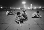 High school students study under the bright lights in Tiananmen Square. Electrical supplies to private residences remained limited at this time. Beijing, 1981.  © Liu Heung Shing